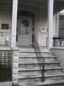 White steps leading to a front porch with black railing in the center and cat sitting at top of the stairs.