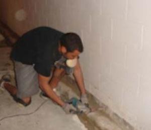 Man in black shirt drills weep holes into base of block walls.