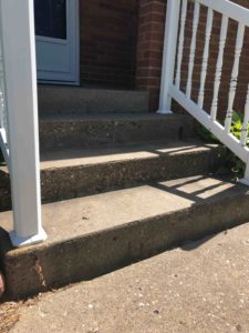 Close up on three concrete steps leading to a front porch with white vinyl railing on each side of steps.
