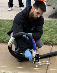 Man in black sweatshirt kneeling near concrete sidewalk holding pump to inject PolyPier.