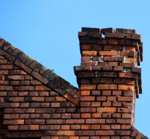 Brick residential chimney on blue sky background