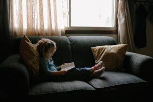 Young girl sitting on gray couch reading a book.