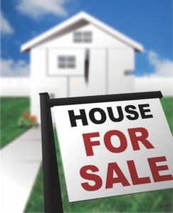 House for sale sign in front of blurred background image of a home.