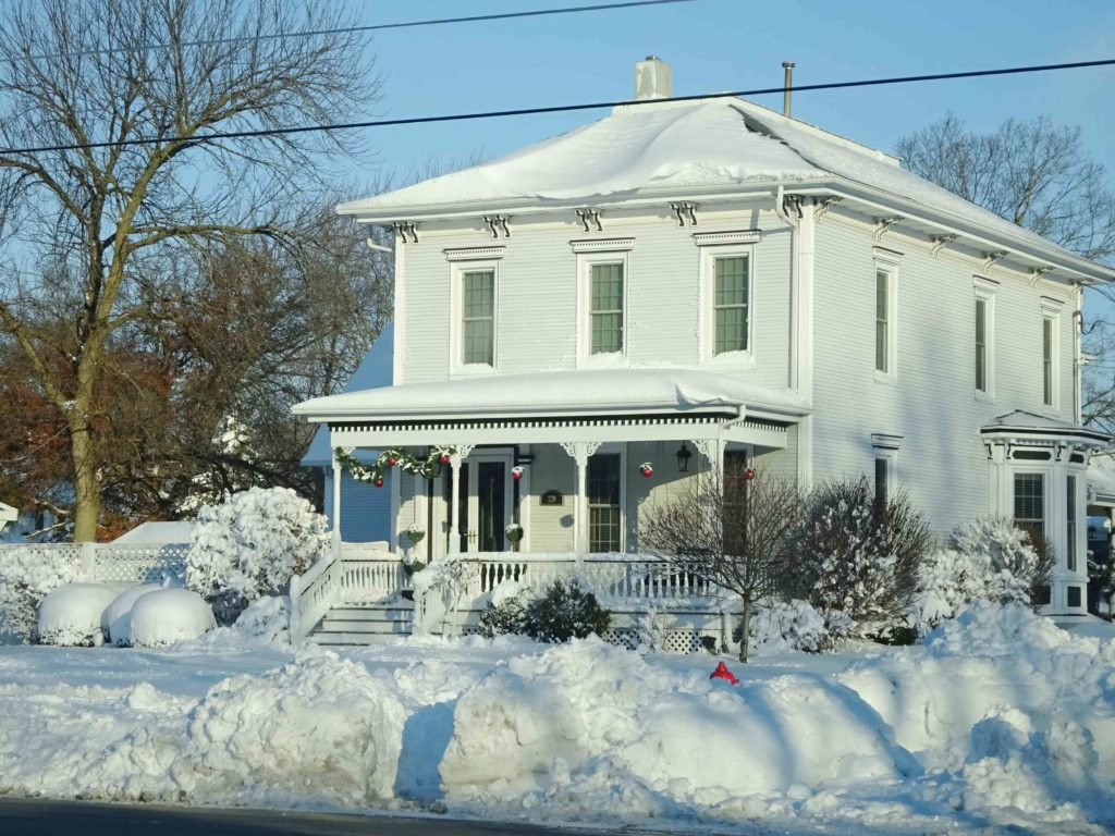 Two store home surrounded by piles of snow