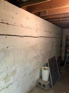 White basement masonry wall with horizontal crack running across entirety of wall.